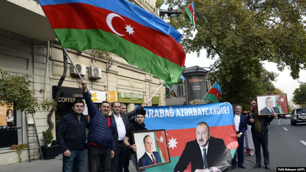People wave the national flag and hold portraits of Azerbaijani President Ilham Aliyev and his father and predecessor Heydar as they celebrate in the streets of Baku on November 10.